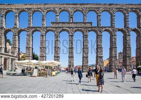 Segovia, Spain - September 21, 2015: Roman aqueduct in Segovia and walking people in Plaza Azoguejo