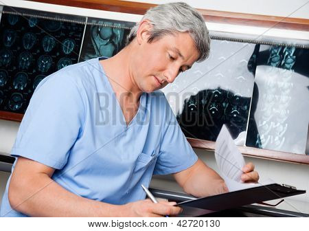 Mature male medical professional in uniform going through document at clinic