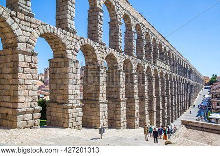 Segovia, Spain - September 21, 2015: Ancient roman aqueduct in Segovia and walking tourists