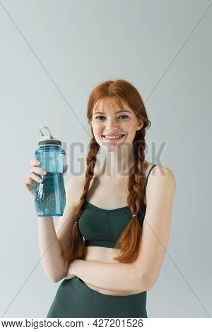 Happy Freckled Sportswoman Holding Sports Bottle Isolated On Grey