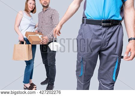 A Courier Delivers A Parcel To A Nice Couple Holding In His Hand A Medical Face Mask On Pandemic Tim