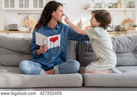 Joyful Mom In Playful Mood Laughing Cuddle With Cute Little Son Hold Gift On Birthday Sitting On Cou