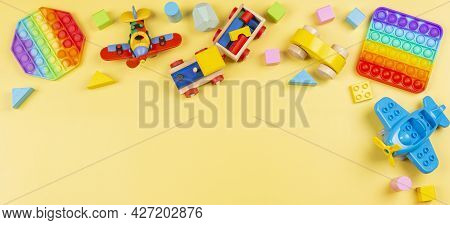 Baby Kid Toys Banner Background With Wooden Blocks, Train, Car, Plane, Pop It Fidget Toy On Yellow B