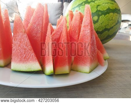 A Close Up Portrait Of A White Plate Full Of Red Pointy Slices Of The Cut Watermelon Next To An Uncu