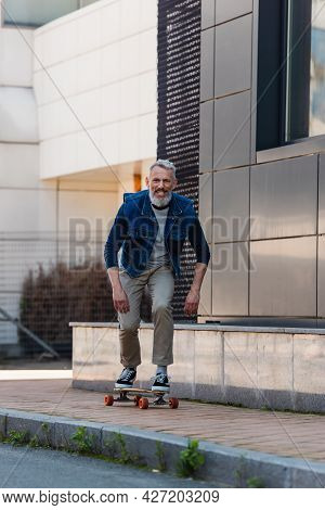 Full Length Of Middle Aged Man Smiling And Riding Longboard On Urban Street