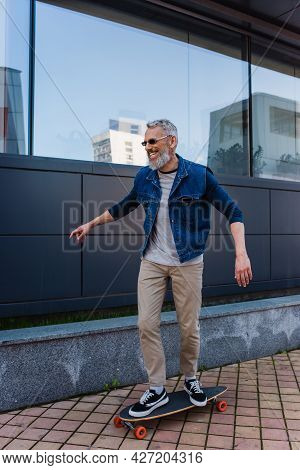 Full Length Of Cheerful And Mature Man Riding Longboard On Urban Street