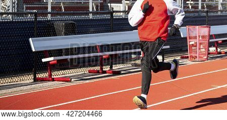 A High School Boy Is Running Fast On A Track During Witer Track Training Wearing A Sweatshirt And Gl
