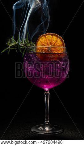 Purple Gin Tonic Cocktail with smoking rozmarine and orange on black background.