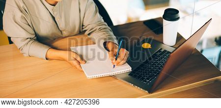 A Woman In Glasses Studying Online With Her Laptop, Writing In Notepad. Easy Online Education With C