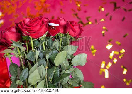The Photo Of Red Roses And A Beautiful Gold Ring Are Symbol Of Marriage Proposal To A Nice Young Wom