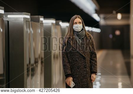 Lady In A Medical Face Mask To Avoid The Spread Of Coronavirus Is Waiting For A Train And Holding A