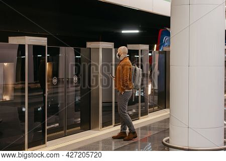 A Man In A Medical Face Mask To Avoid The Spread Of Coronavirus Is Holding A Phone While Waiting For