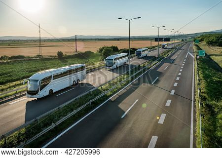 Series Of Modern White Buses Traveling On A Wide Highway In A Rural Backdrop. Convoy Of Buses. Highw