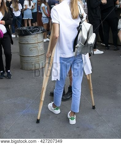 A Girl With A Broken Leg In A Cast On Crutches Came To The Market. Travel Of People With Disabilitie