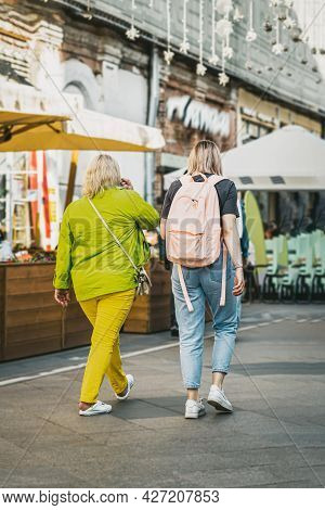 Rear View Of Young Women Walking Together Along A City Street. Lifestyle Concept