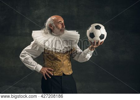 Elderly Gray-haired Man, Actor Posing With Football Ball Isolated On Dark Vintage Background. Retro