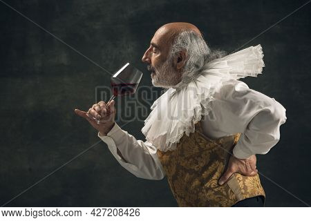 Elderly Gray-haired Man, Medieval Hystorical Person, Actor Drinking Wine Isolated On Dark Vintage Ba