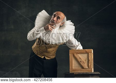 Elderly Gray-haired Man, Actor Or Magician Isolated On Dark Vintage Background. Retro Style, Compari