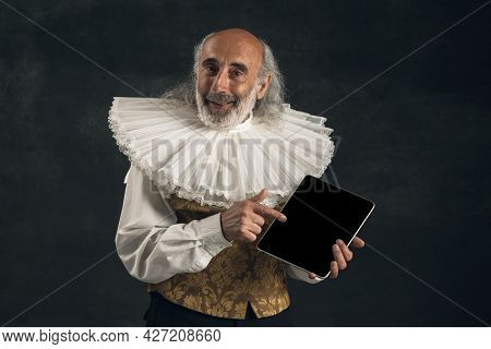 Portrait Of Elderly Gray-haired Man, Medieval Hystorical Person, Actor Using Tablet Isolated On Dark