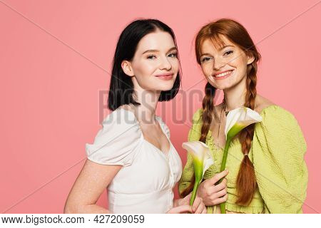 Smiling Women With Freckles And Vitiligo Holding Flowers Isolated On Pink