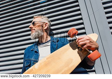 Low Angle View Of Bearded Middle Aged Man In Sunglasses Holding Longboard