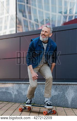 Full Length Of Smiling Middle Aged Man Riding Longboard On Urban Street