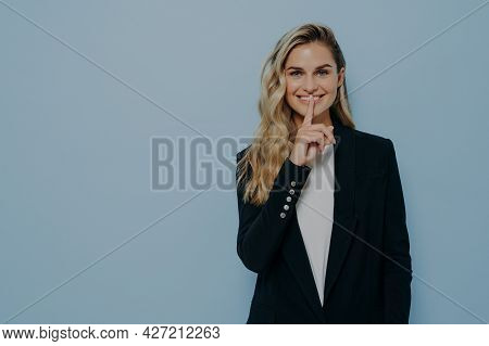 Cheerful Beautiful Young Woman In Black Blazer Keeps Finger On Lips And Asking To Keep Something In