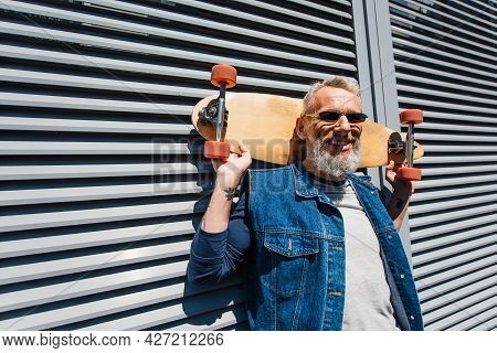 Bearded Middle Aged Man In Sunglasses Smiling And Holding Longboard