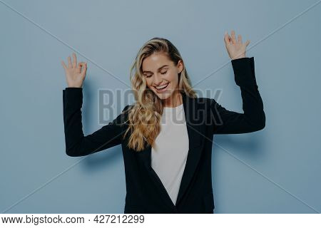 Portrait Of Carefree Happy Woman With Blonde Dyed Hair Raising Her Arms And Dancing With Closed Eyes