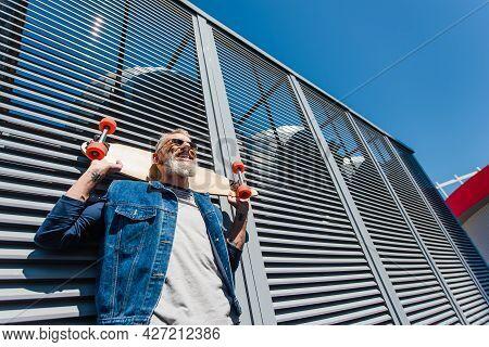 Low Angle View Of Positive And Middle Aged Man Holding Longboard On Street
