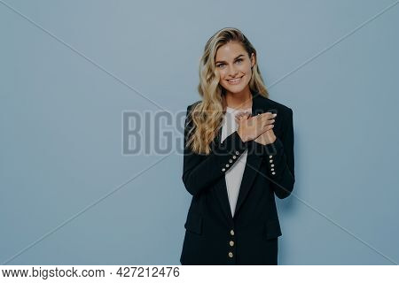 Young Lovely Woman With Blond Hair In Black Blazer Expressing Love And Admiration While Holding Both