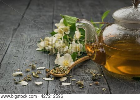 A Glass Teapot With Fresh Tea Made Of Jasmine Petals On A Wooden Table. An Invigorating Drink That I