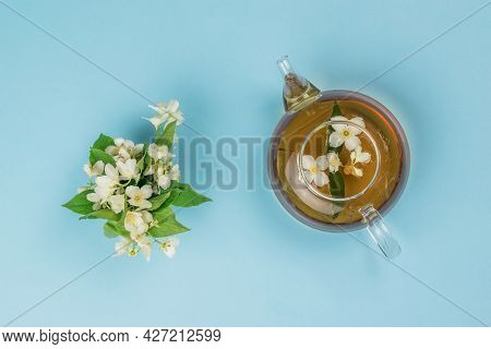 Jasmine Flowers And A Teapot With Jasmine Tea On A Blue Background. An Invigorating Drink That Is Go