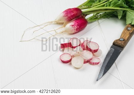 A Knife With A Wooden Handle And Fresh Radishes On A White Wooden Table. A Fresh Crop Of Radishes.