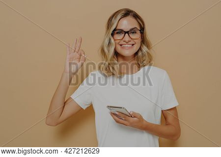 Everything Ok. Young Happy Woman Smiling At Camera And Showing Okay Gesture With Modern Smartphone I