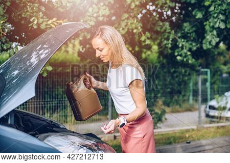 A Woman Is Holding A Bottle Of Motor Oil In Her Car.