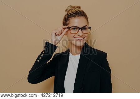 Portrait Of Happy Satisfied Female Teacher In Classic Black Suit Smiling Broadly And Adjusting Her G