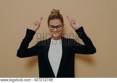 Hopeful Young Woman Standing With Hands Up And Crossed Fingers In Luck Gesture, Female In Black Styl