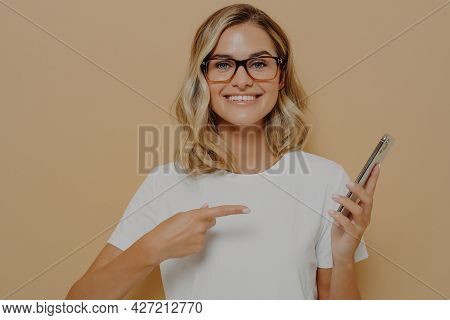 Portrait Of Impressed, Excited Young Blond Woman Showing Something Awesome On Display, Pointing On M