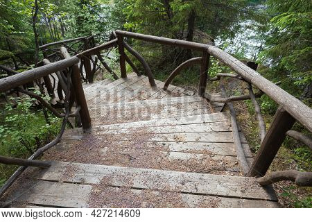 Wooden Stairway Goes Down In The Forest On A Summer Day