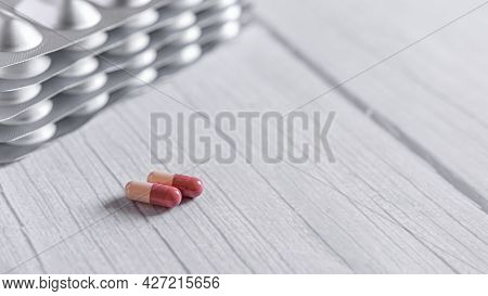 Red-white Medicine Capsules On Wooden White Table Background. Top View With Copy Space.