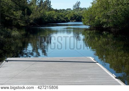 Looking Out From The End Of An Empty Pier Into The Imperial River Surrounded By Florida Wilderness.