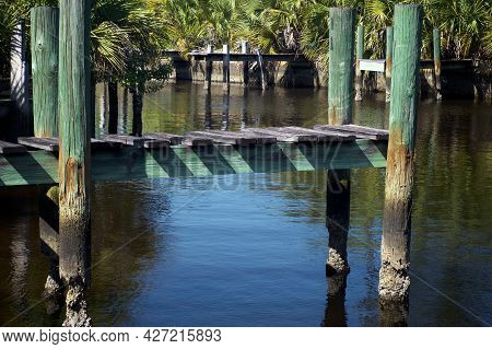 View Of Old Rotting Abandoned Boat Docks On Overgrown Canal In Bonita Springs Florida.