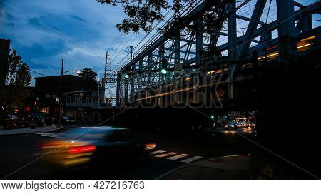 NORWALK, CT, USA-JULY 17, 2021: Evening lights at busy Washington street in downtown with railroad bridge