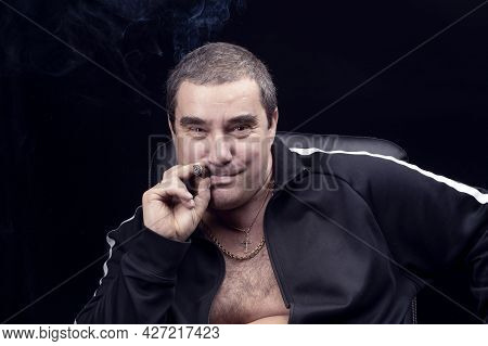 A Funny And Charming Adult White Man Smokes A Cigar And Laughs And Smiles Looking At The Camera. The