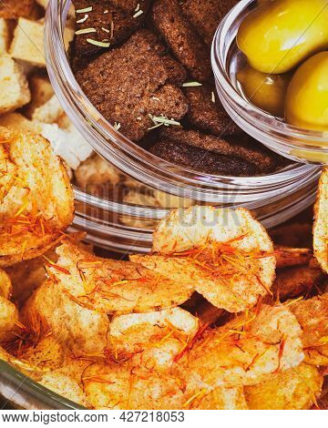 Rye Crackers, Wheat Crackers, Potato Chips With And Green Olives In Glass Bowls On A White Table