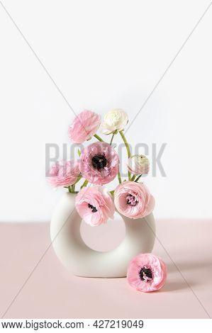 Tender Ranunculus Flowers In Trendy Ceramic Minimalistic Vase On Pink Background With Copy Space. Bu