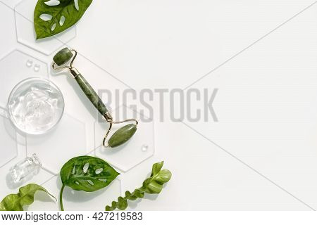 Moisturizer, Green Jade Face Roller On Oval Ice With Ice Cubes And Exotic Leaves. Monstera Adansonii