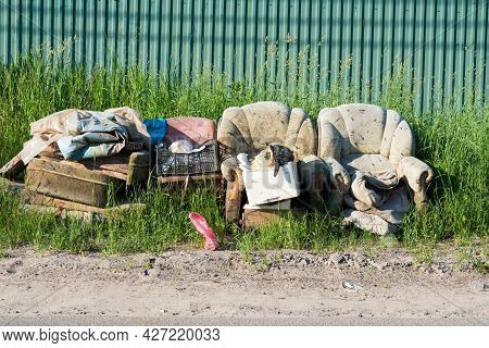 An Old Sofa Along With Other Rubbish Sits On The Side Of The Road. Trash Prepared For Disposal
