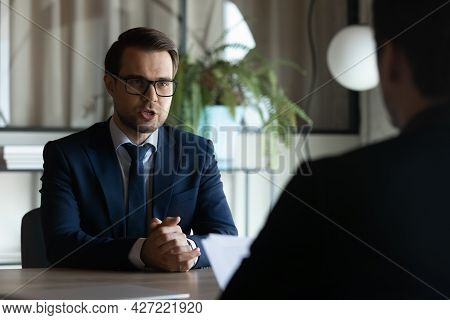 Serious Confident Employer And Candidate Sitting Opposite At Job Interview